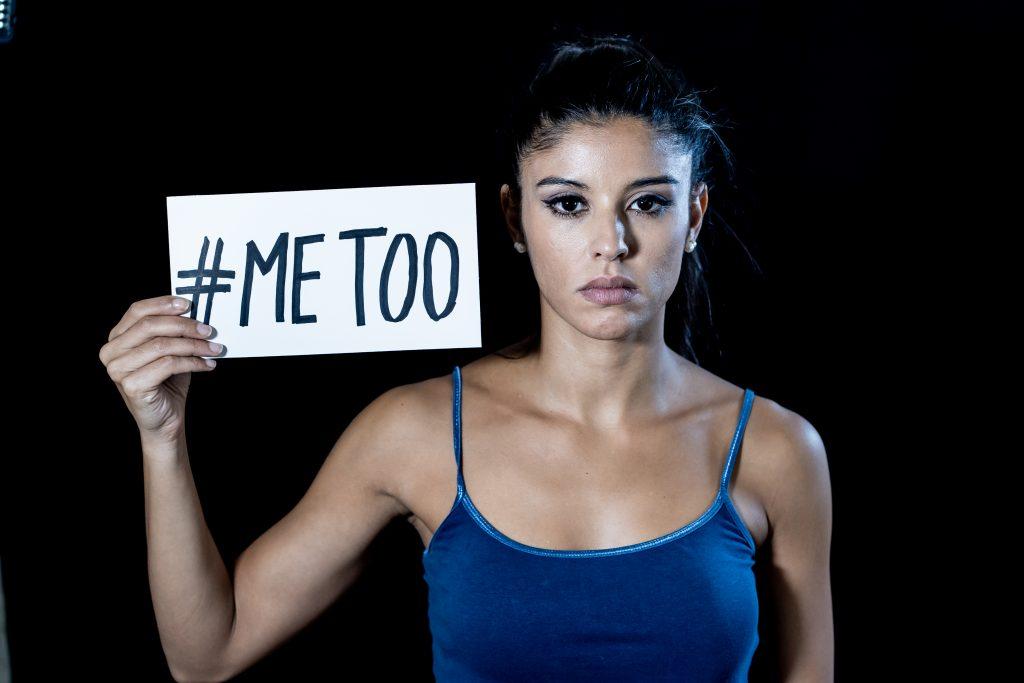 Na fotografia podemos ver uma mulher com um cartaz do movimento Me Too contra a violência sexual e a violência de género