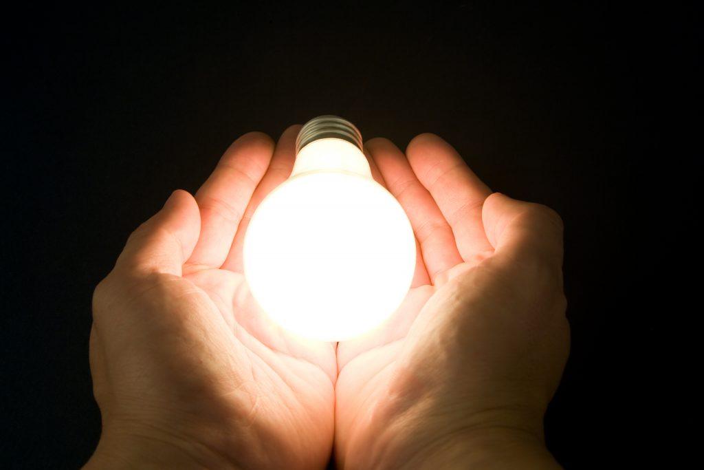 Na imagem estão duas mãos a segurar uma lâmpada acesa