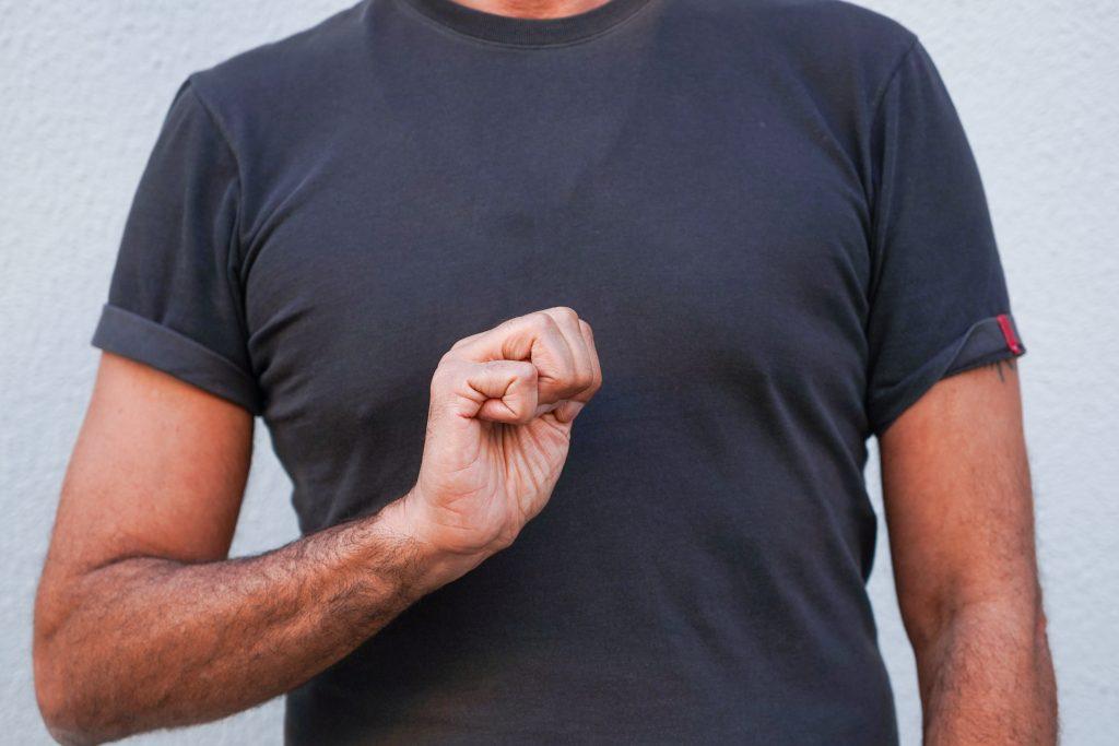 Figura humana representa com a sua mão a letra S no alfabeto da Língua Gestual Portuguesa